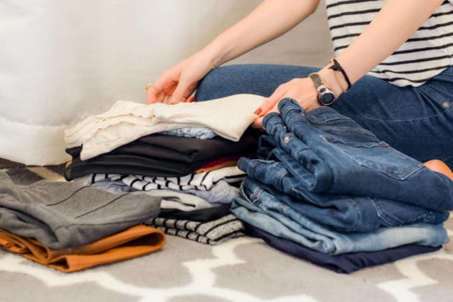 woman sitting on the floor folding clothes
