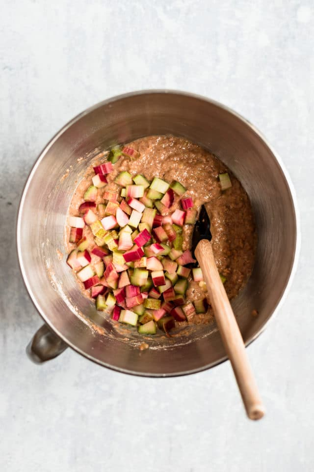 mixing chopped rhubarb with quick bread batter in a silver mixing bowl