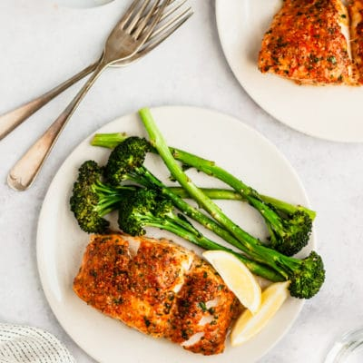 baked cod and broccoli on a white plate served with lemon slices