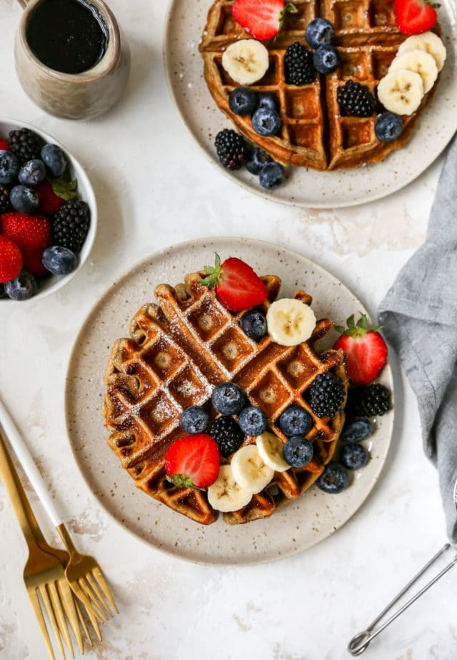protein waffles served with berries and a dusting of powdered sugar