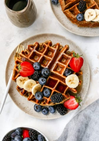 protein waffles drizzled with syrup and topped with fresh fruit