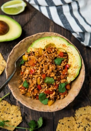 easy unstuffed bell pepper skillet in a bowl topped with avocado slices and fresh cilantro