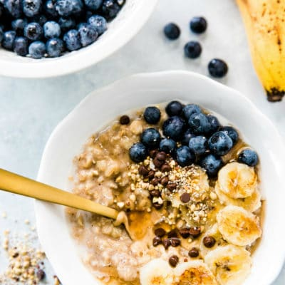 Best Banana Bread Oatmeal served in a white bowl and topped with blueberries