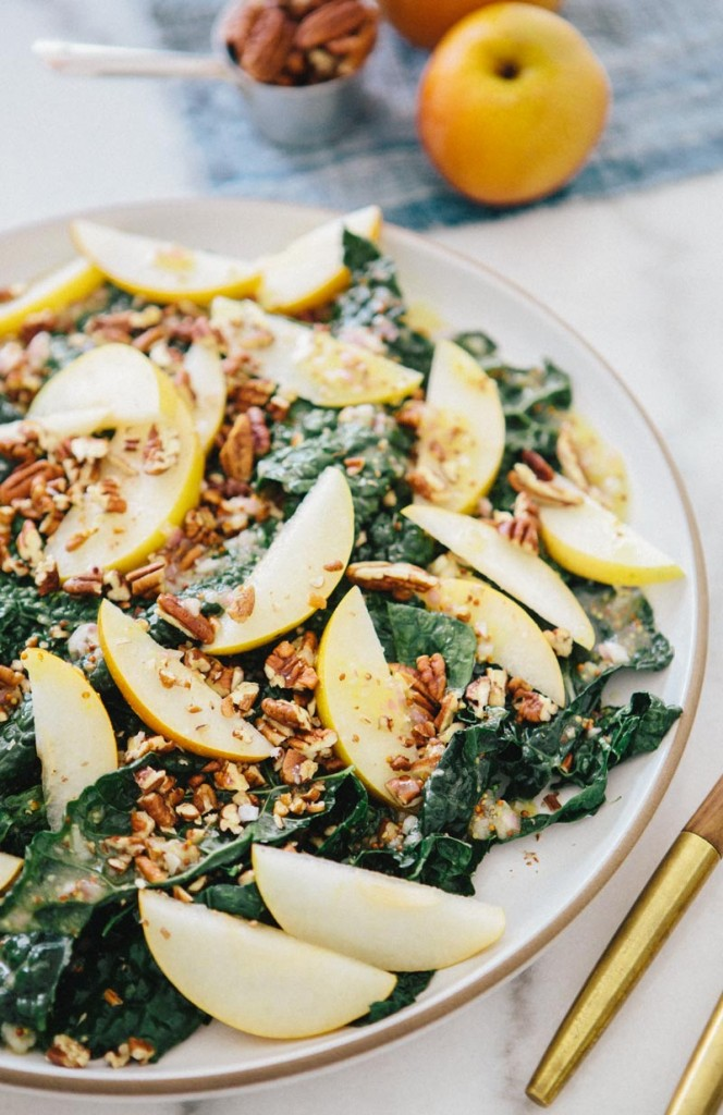 kale salad topped with sliced pear and chopped pecans on a white plate