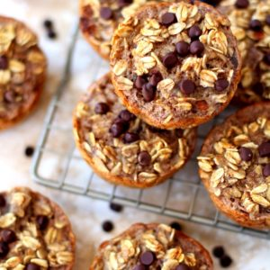 oatmeal cups topped with chocolate chips stacked on a wire cooling rack