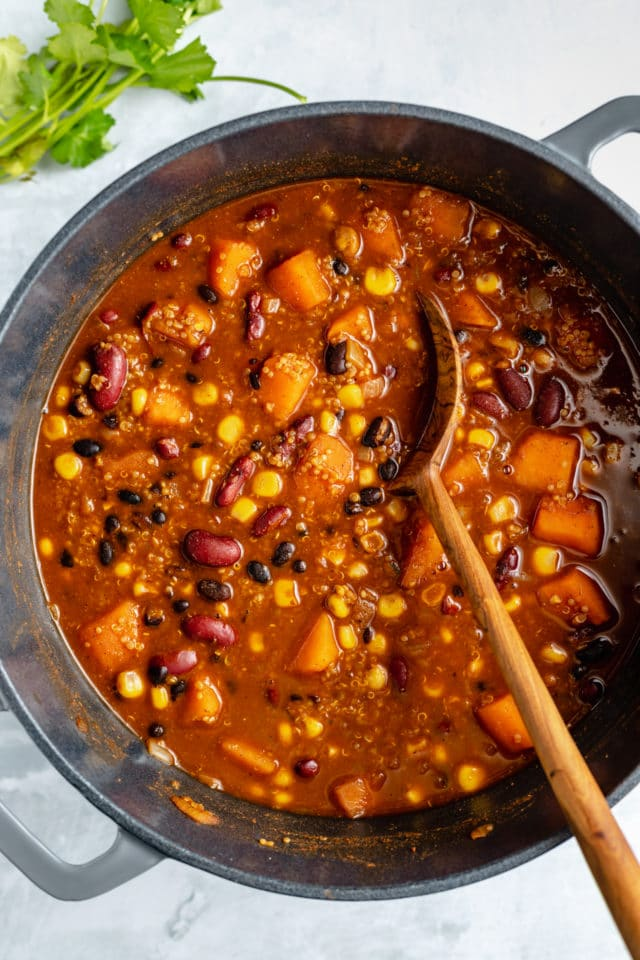 stirring quinoa bean chili with a wooden spoon