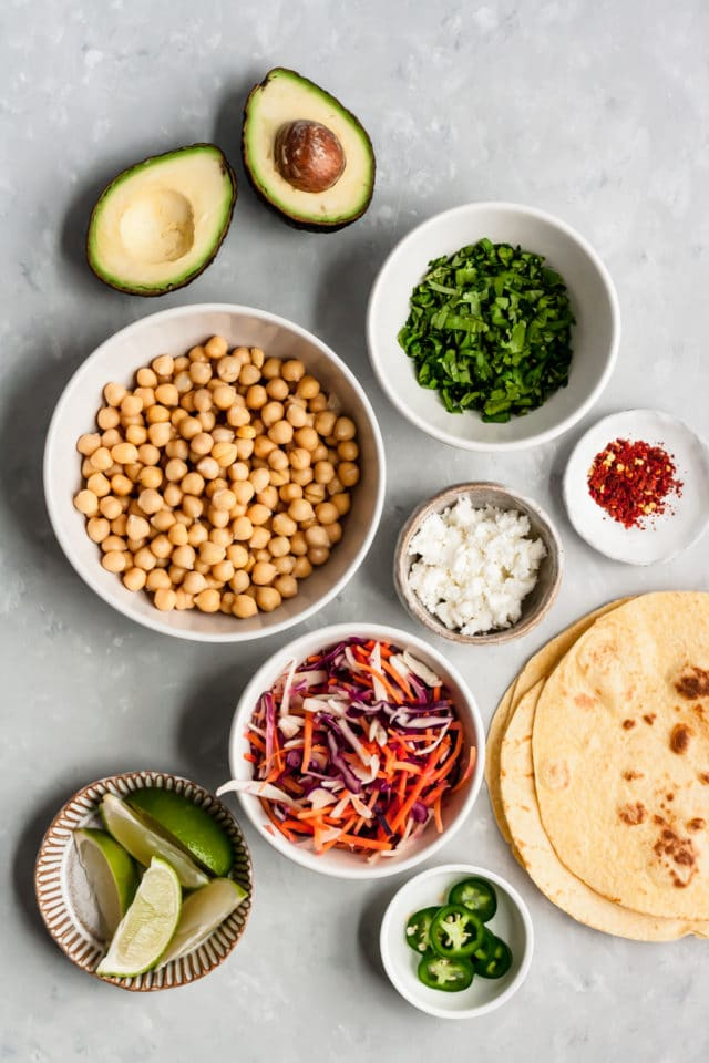 all of the ingredients in small bowls for Chickpea Avocado Tacos