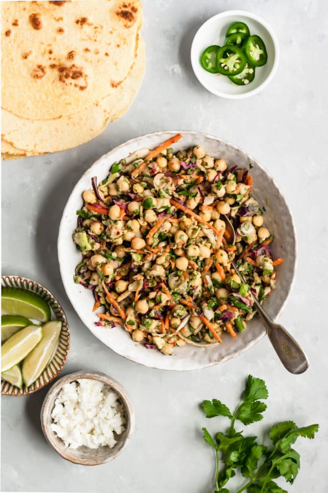 chickpeas, avocado, sliced carrot and cilantro mixed in a white bowl