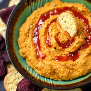 Carrot Ginger Hummus with a cracker on top