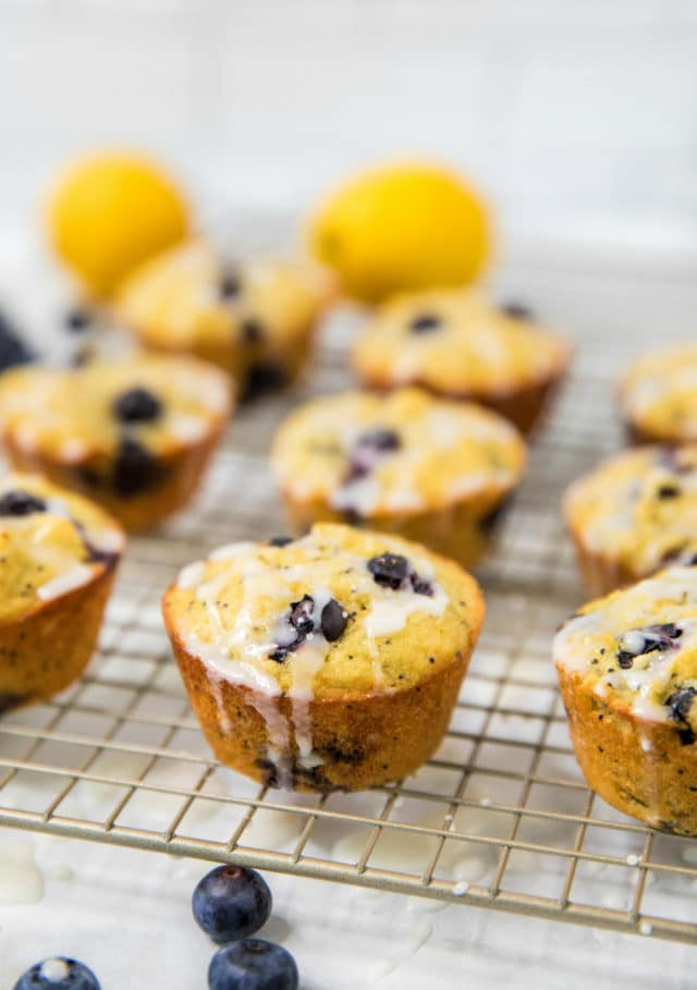 lemon poppyseed blueberry muffins on a cooling rack with lemon glaze drizzling down