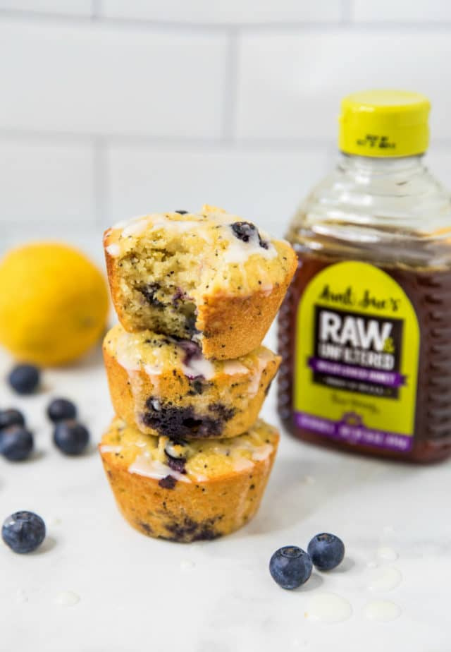three lemon blueberry muffins stacked near a lemon and a bottle of honey