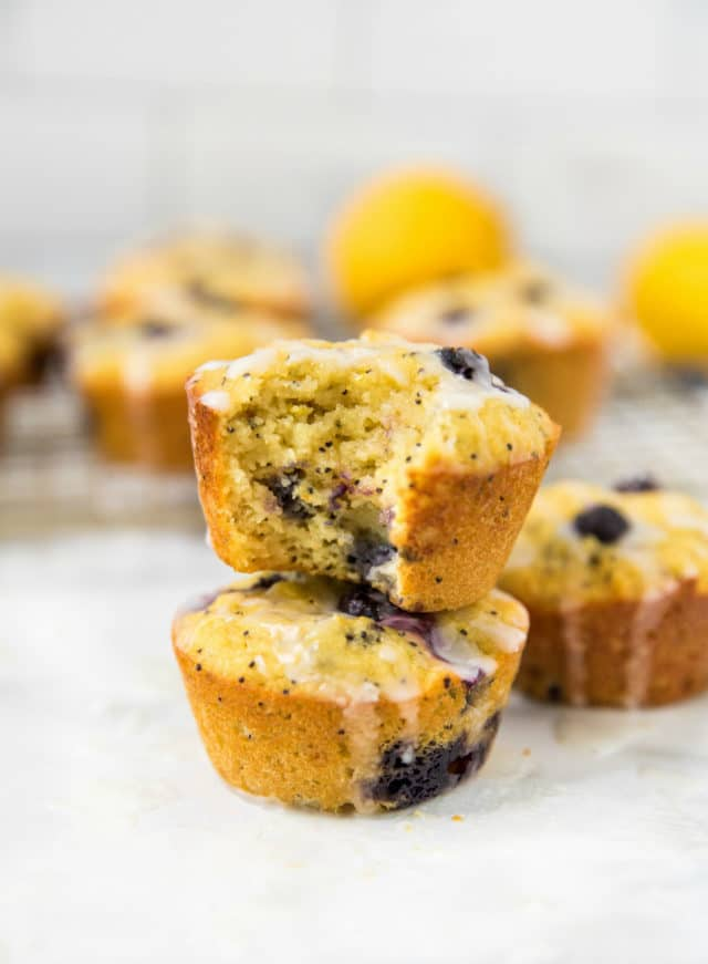 two lemon blueberry muffins with icing stacked