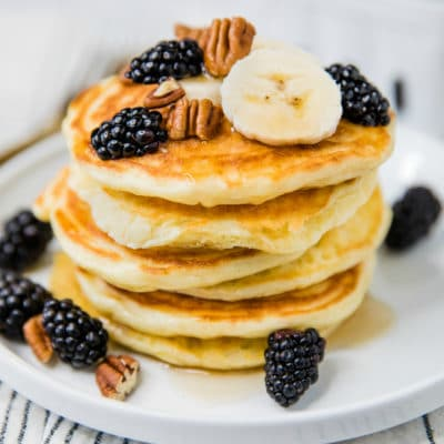 fluffy pancakes stacked on a white plate