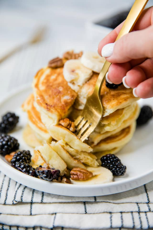 woman's hand cutting into a stack of pancakes with a gold fork