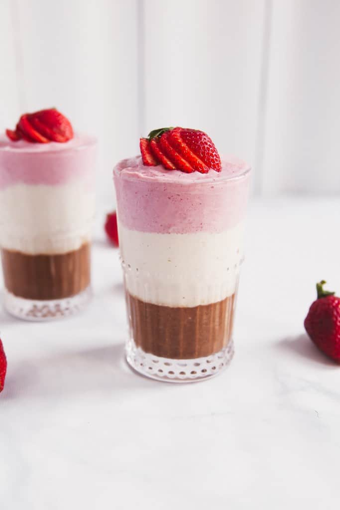 Layered banana split protein smoothies perfect for after a workout or as a late-night treat. They taste exactly like a banana split! Great drizzled with a little peanut butter or topped with coconut whipped cream.