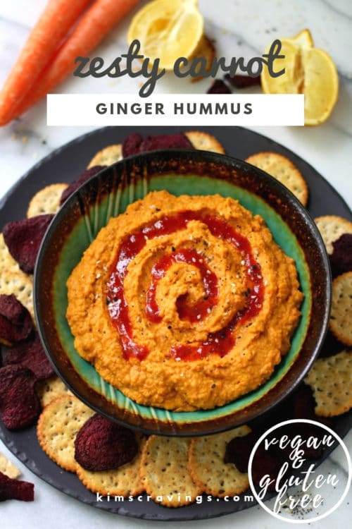carrot hummus with a swirl of Sriracha sauce served with crackers around the dish
