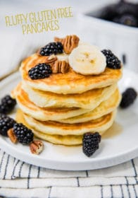 pancakes on a white plate topped with blackberries and pecans