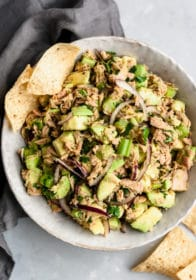 Easy Avocado Tuna Salad in a large white serving bowl with a few tortilla chips on the side