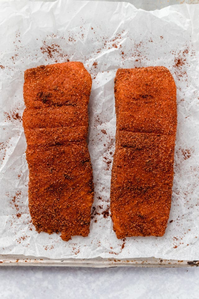 salmon filets seasoned on parchment paper