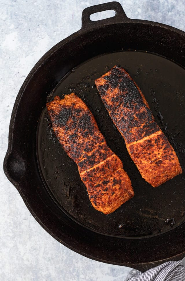 salmon filets cooking on cast iron skillet