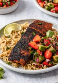 blackened salmon on a plate with strawberry avocado salsa and rice