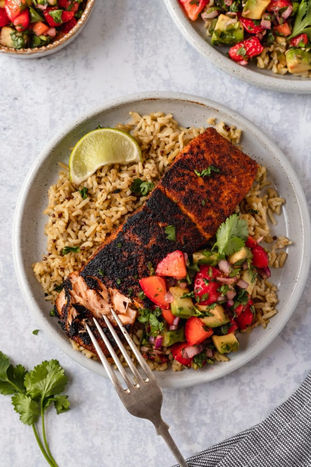 fork on plate with blackened salmon and strawberry salsa over rice