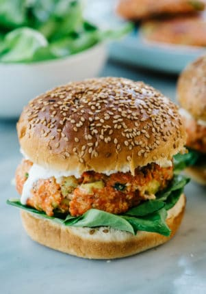 Salmon burger on a sesame seed bun with ranch and spinach