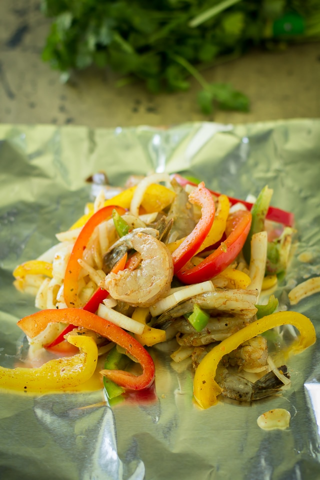 Grilled Shrimp Fajita Foil Packets are so easy and delicious. Perfectly cooked in foil - juicy shrimp, tender bell peppers and onions can be wrapped into a warm tortilla for a super fast dinner, that's packed with incredible flavor!