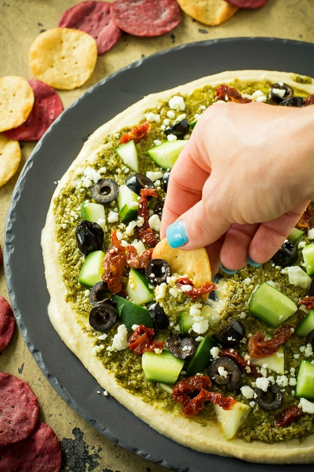 A healthy, tasty, easy Mediterranean layer dip recipe that is a great appetizer or wholesome snack. Loaded with goodies, like hummus, pesto,  feta, olives and sun-dried tomatoes.