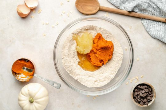 mixing dry and wet ingredients for pumpkin cookies in a mixing bowl