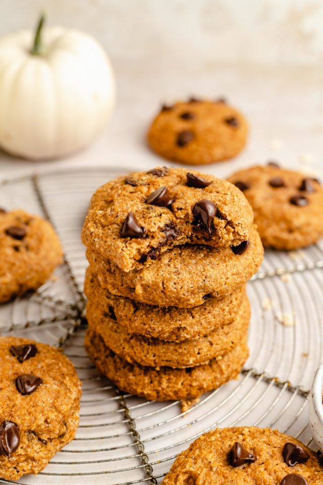 pumpkin cookies stacked on a wire cooling rack