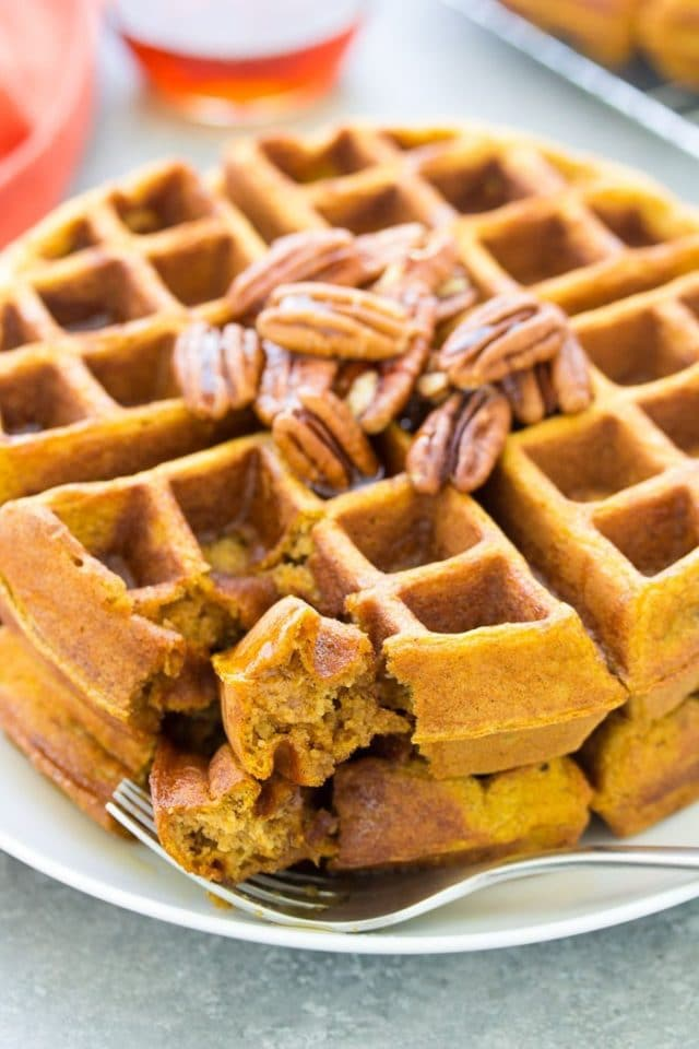 healthy pumpkin waffles topped with pecans and syrup