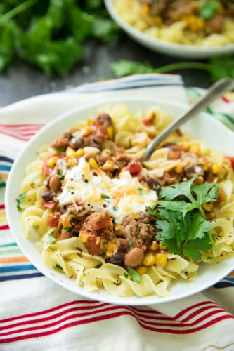 Looking for an EASY dinner that is extremely delicious too? This Bison Taco Chili Over Noodles is your recipe! It's like your favorite taco turned into a cozy chili recipe!