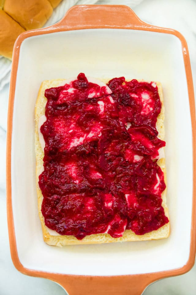 Cranberry sauce spread over turkey rolls