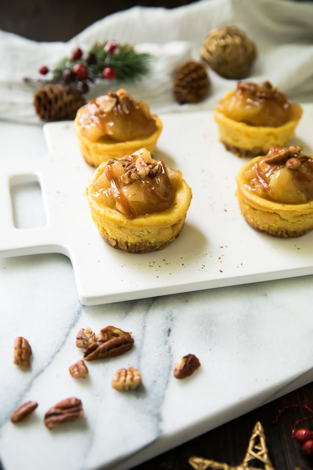 Easy Salted Caramel Mini Cheesecakes are the best holiday treat idea! Luscious mini cheesecakes get topped with cinnamon apples and a drizzle of salted caramel to make all of your dessert dreams come true!