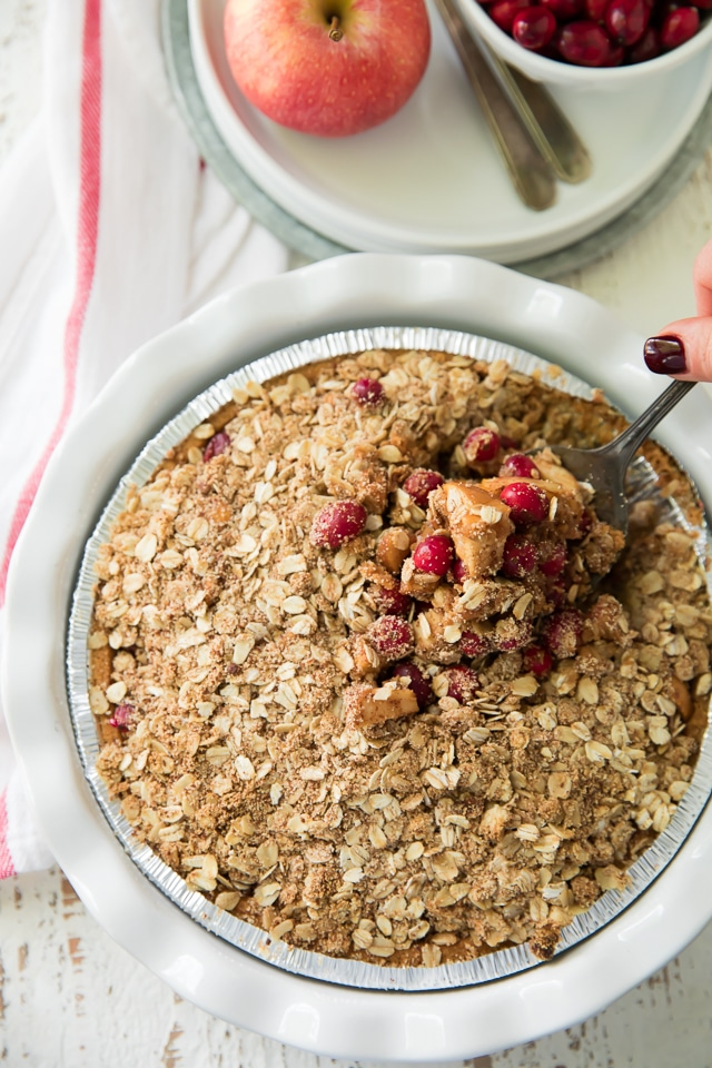 This Gluten Free Cranberry Apple Crumble Pie has all of the warmth, spice and sweet flavor of the holiday season. Also, it's ridiculously simple to throw together and will make the perfect addition to your festive dessert spread!
