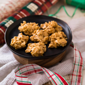 No Bake Peanut Butter Cookies on a black plate with Christmas wrapping paper and ribbon