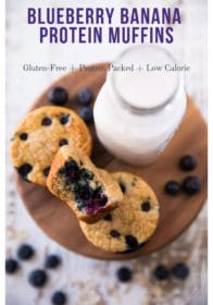 Blueberry muffins on a wooden serving plate near a glass of milk