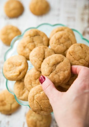 Snickerdoodle Cookies on a glass plate with a woman's hand reaching for one