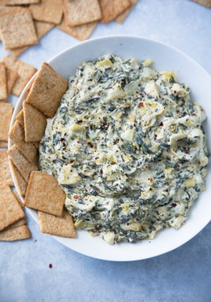 Skinny Slow Cooker Spinach Artichoke Dipserved in a white bowl with WHEAT THIN crackers on the side