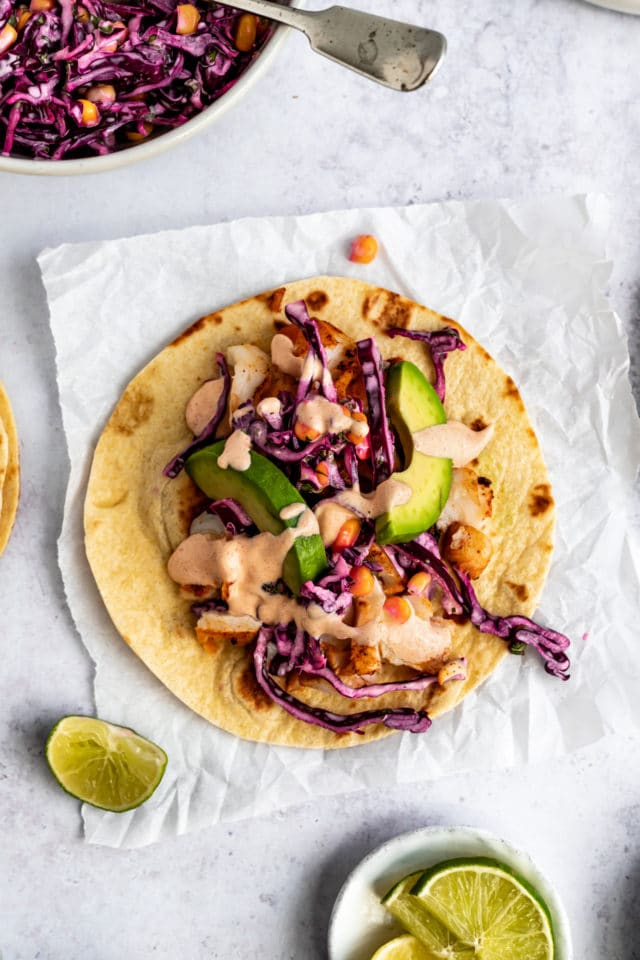 fish taco served on a corn tortilla with slaw and fish taco sauce