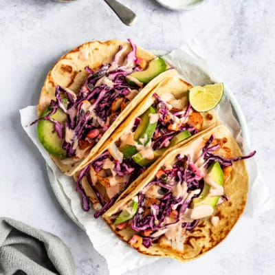 three cod fish tacos topped with slaw, sauce and sliced avocado