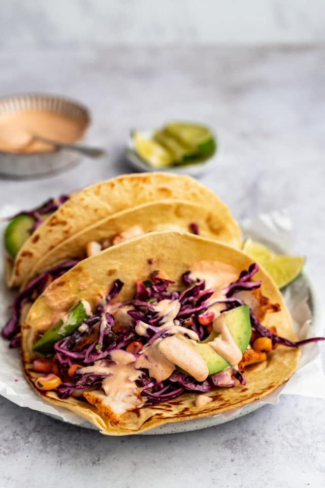 fish tacos made with cod, purple cabbage slaw, sauce and sliced avocado
