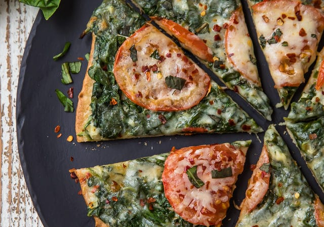 This Skinny Garlic Spinach White Pizza has everything you could ever want or enjoy in a pizza, without all the stuff your body doesn't love! This pizza is 100% clean eating friendly, with a sauce that is bursting with flavor! But the best part about this pizza!?! The crust!!!