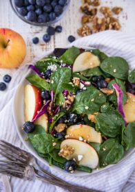 spinach salad topped with blueberry and apple slices