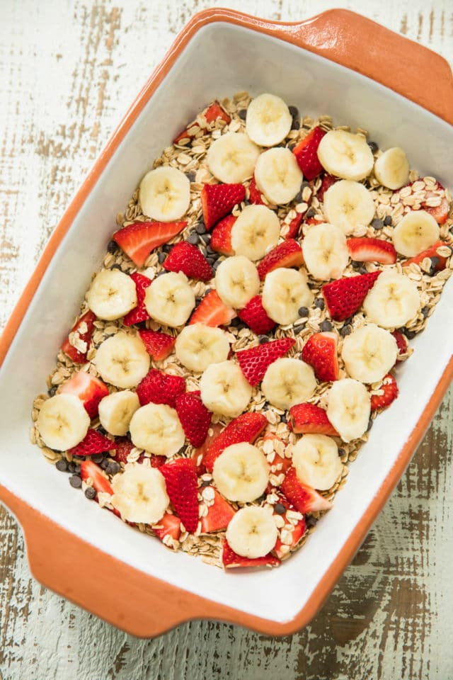 mixing ingredients for the Easy Strawberry Banana Baked Oatmeal is so delicious; studded with fresh strawberries, banana slices and sweet chocolate chips. It's one of our favorites and is sure to become one of yours too!