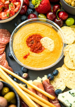 cracker dipped in Sabra Roasted Red Pepper Hummus