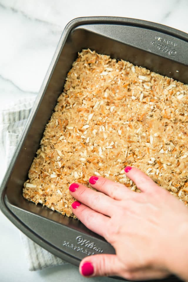 pressing almond flour and pretzel mixture into baking pan for Skinny Strawberry Pretzel Dessert