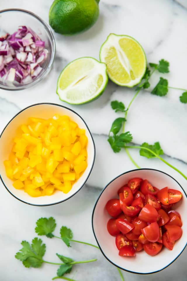 ingredients for Healthy Sweet Potato Burrito Bowls; red onion, limes, chopped yellow bell pepper and sliced cherry tomatoes
