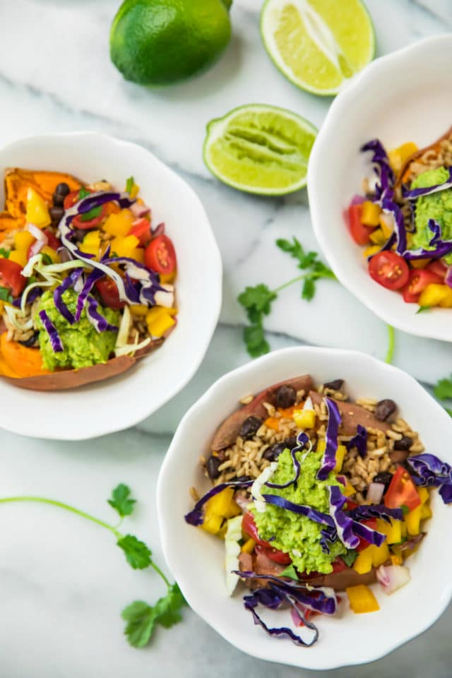 overhead of Healthy Sweet Potato Burrito Bowls in white bowls, topped with guacamole and purple cabbage